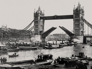 Historic image of Tower Bridge and the upper Pool of London filled with barges